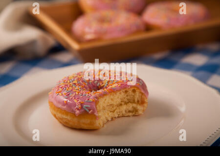 Pink Donut on a plate with bite taken out - Stock Photo