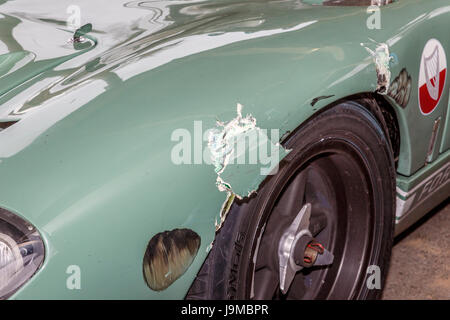 Close-up detail of impact damage on 1965 Ford GT40 front nearside wing during the Alan Mann Trophy race at Goodwood - Stock Photo