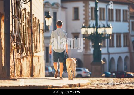 Morning in the city. Young man walking with his dog on the old street at golden sunrise. Prague, Czech Republic - Stock Photo