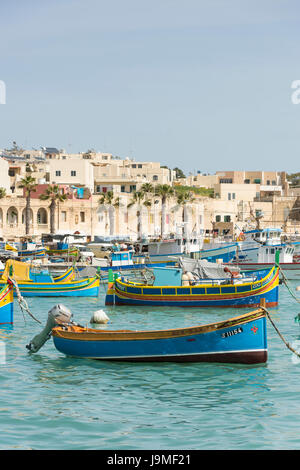 traditional Maltese fishing boat or luzzu, brightly painted in the harbour of Marsaxlokk in Malta - Stock Photo