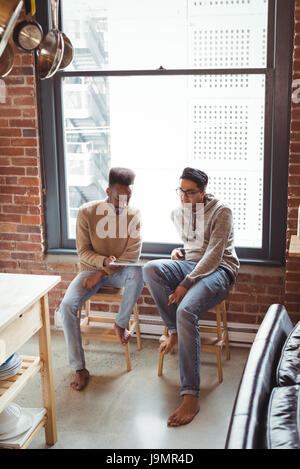 Gay couple using digital tablet while sitting on stool at home - Stock Photo
