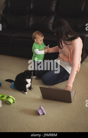 Mother using laptop and looking at her daughter holding mobile phone in living room - Stock Photo