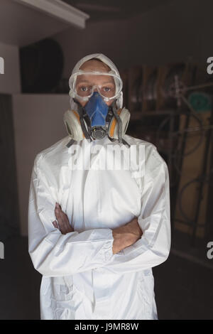 Portrait of employee wearing gas mask while standing at bicycle workshop - Stock Photo