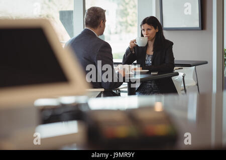 Businesswoman and businessman having coffee in office cafeteria - Stock Photo