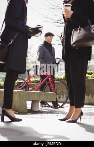 Businessman walking with his cycle while woman interacting with each other in office premises - Stock Photo