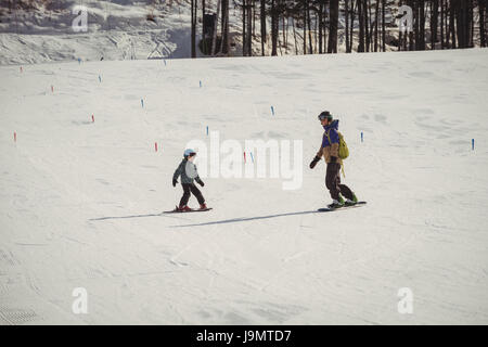 Mother and daughter skiing on snowy alps during winter - Stock Photo