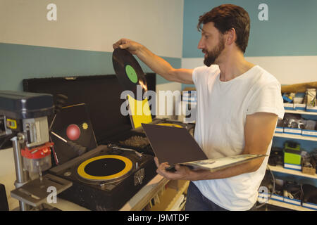Worker holding record by turntable at bicycle workshop - Stock Photo