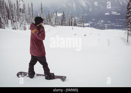 Man skiing on snowy alps in ski resort during winter - Stock Photo