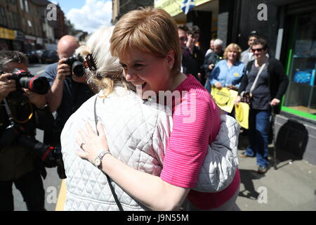 First Minister Nicola Sturgeon (right) is greeted by Helen, the mother of the SNP's local candidate Mhairi Black, - Stock Photo