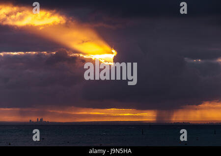 From Rottnest Island to Perth across the ocean with dramatic sun rays bursting through clouds. - Stock Photo