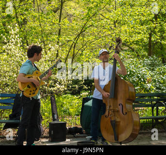 New York, NY USA -- April 28, 2017 -- An electric guitar and upright Bass player performing musically  in New York's - Stock Photo