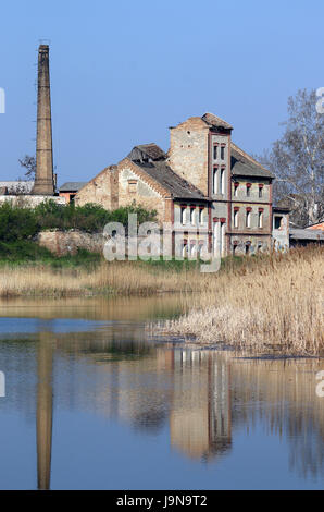 old ruined factory on lake - Stock Photo