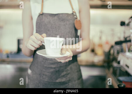 Asian women Barista holding a cup of coffee - Working woman small business owner food and drink cafe concept - Stock Photo