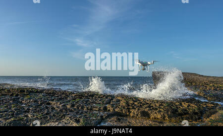 Drone hovering in front of ocean waves crashing against rocks - Stock Photo
