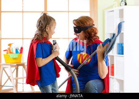 Happy woman with kid cleaning room and have a fun. Mother and child girl playing together. Family in Superhero costumes. - Stock Photo