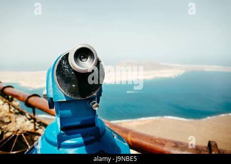 Telescope and panoramic view at La Graciosa Island from Mirador del Rio viewpoint. - Stock Photo