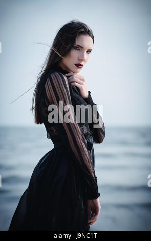Beautiful sad goth girl in black dress standing on the sea beach - Stock Photo