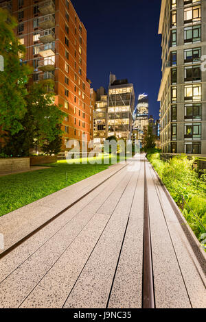Highline promenade and old railway tracks at twilight with high-rises and building lights in Chelsea. Manhattan, - Stock Photo