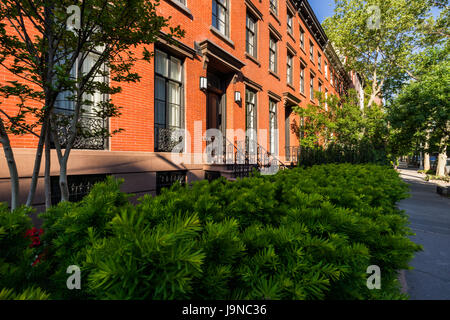 Nineteenth century townhouses with brick facades and wrought iron railings. Summer in Chelsea. Manhattan, New York - Stock Photo