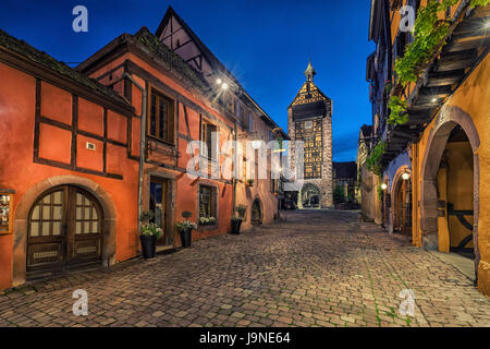 Evening street with Dolder Tower and traditional colorful half-timbered houses in Riquewihr village on alsatian - Stock Photo