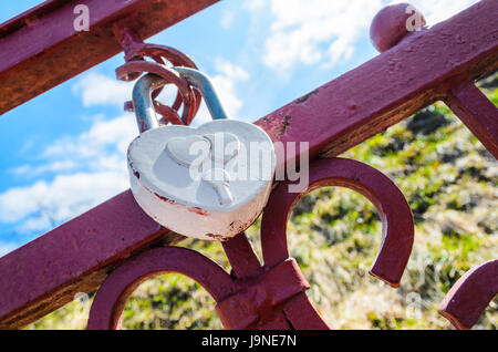 A white heart-shaped love padlock locked to a bridge by newlyweds to symbolize their love - Stock Photo