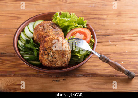 scotch egg with vegetables on a wooden background - Stock Photo