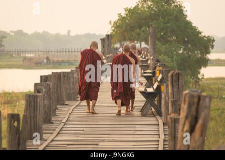 Monks waking at sunrise over U Bein Teak Bridge, Amarapura, Myanmar. - Stock Photo