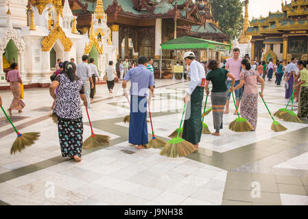 Cleaning the floor with the softest brooms ever. Shwedagon Pagoda, Yangon, Myanmar. - Stock Photo