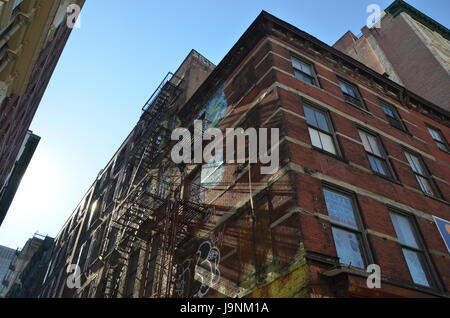 sunlight shines through a chinatown building fire escape on red brick building - Stock Photo