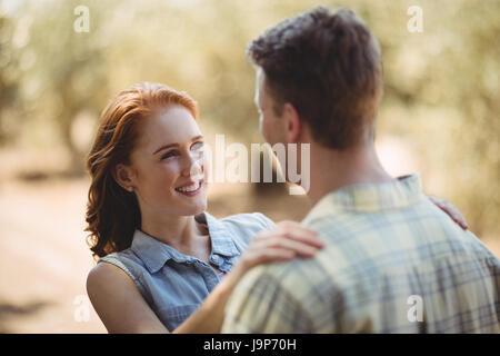 Close up of happy young couple looking at each other at olive farm - Stock Photo