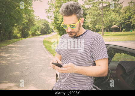Tourist guy standing next to car and looking at smart phone. Driver using road map navigation app or calling road - Stock Photo