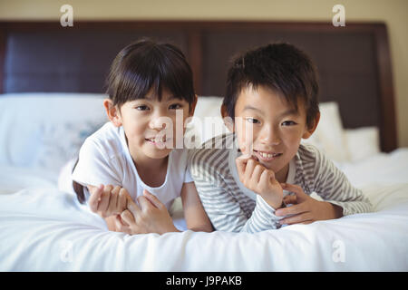 Siblings relaxing on bed in bedroom at home - Stock Photo