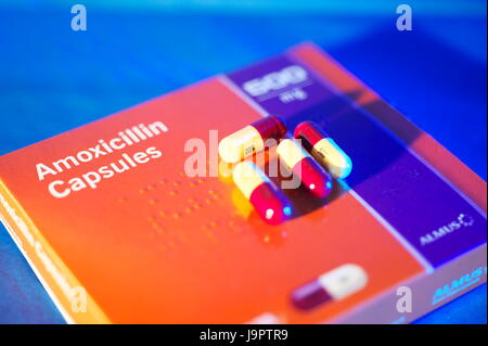 Still life dramatic lighting of Amoxicillin tablets in and out of packets, used for bacterial infections - Stock Photo