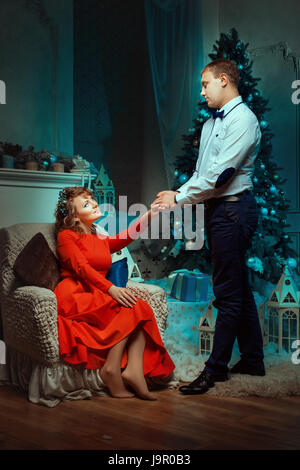 Man holding a woman hand in his hands and looks at her tenderly. Christmas tree decorated with balls. - Stock Photo