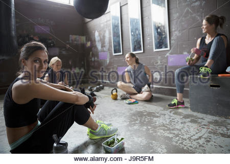 Portrait confident women resting, eating snack post workout at gritty gym - Stock Photo