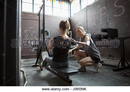 Personal trainer guiding woman weightlifting, doing seated rows in gritty gym - Stock Photo