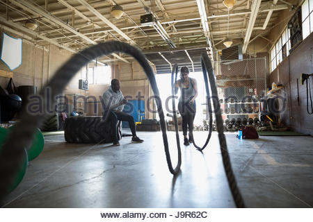 Male personal trainer watching female client doing crossfit battling ropes exercise in gym - Stock Photo