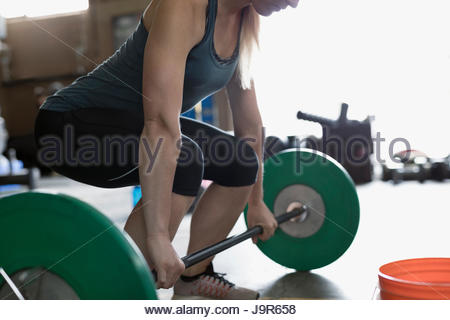 Strong woman weightlifting, doing barbell deadlift at gym - Stock Photo