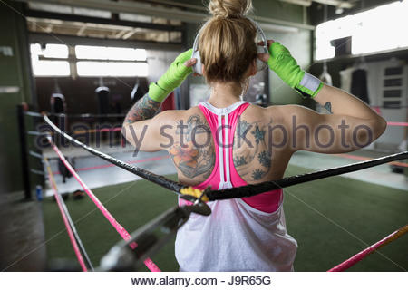 Rear view tattooed woman boxer listening to music with headphones in boxing ring at gym - Stock Photo