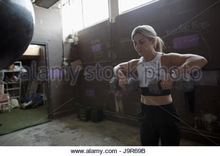 Woman weightlifting with dumbbells in gritty gym - Stock Photo