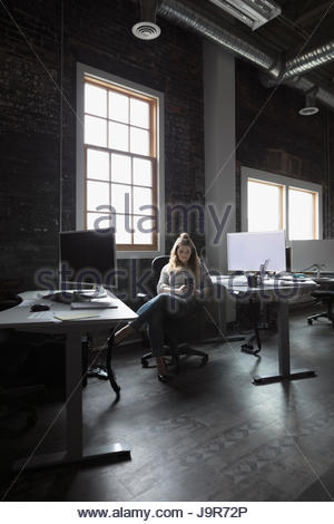 Creative businesswoman texting with smart phone in open plan office - Stock Photo
