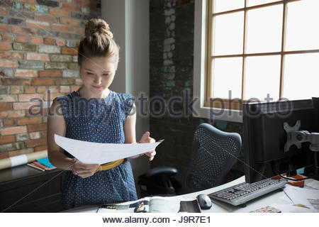 Female architect reviewing blueprint in office - Stock Photo