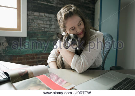Smiling creative businesswoman hugging dog in lap at desk - Stock Photo