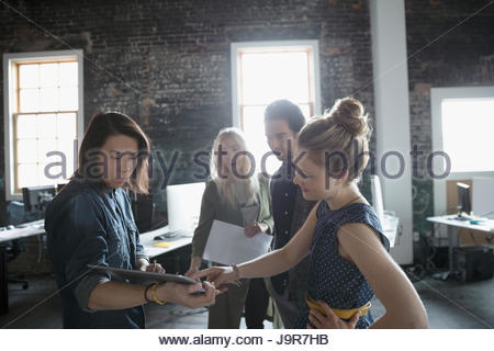 Creative business people with digital tablet meeting in office - Stock Photo