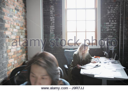 Female designer reviewing proofs at desk in office - Stock Photo