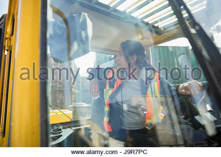 Female forklift driver inside forklift in industrial container yard - Stock Photo