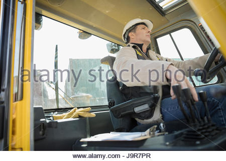 Male worker driving forklift in container yard - Stock Photo