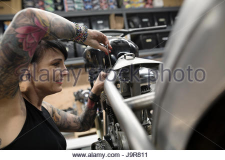 Female motorcycle mechanic with tattoos fixing motorcycle in auto repair shop - Stock Photo