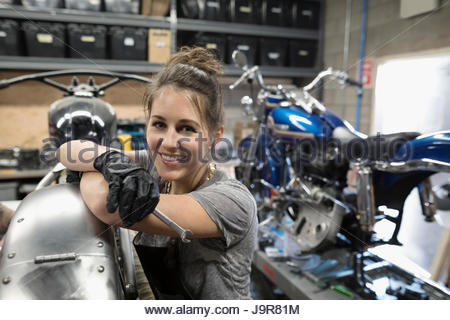 Portrait smiling, confident female motorcycle mechanic fixing motorcycle in auto repair shop - Stock Photo