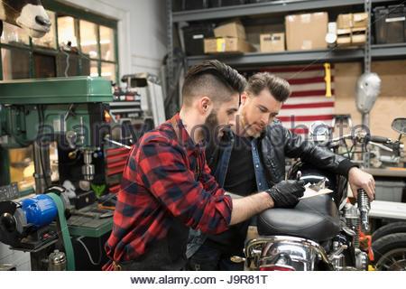 Motorcycle mechanics fixing motorcycle in auto repair shop - Stock Photo